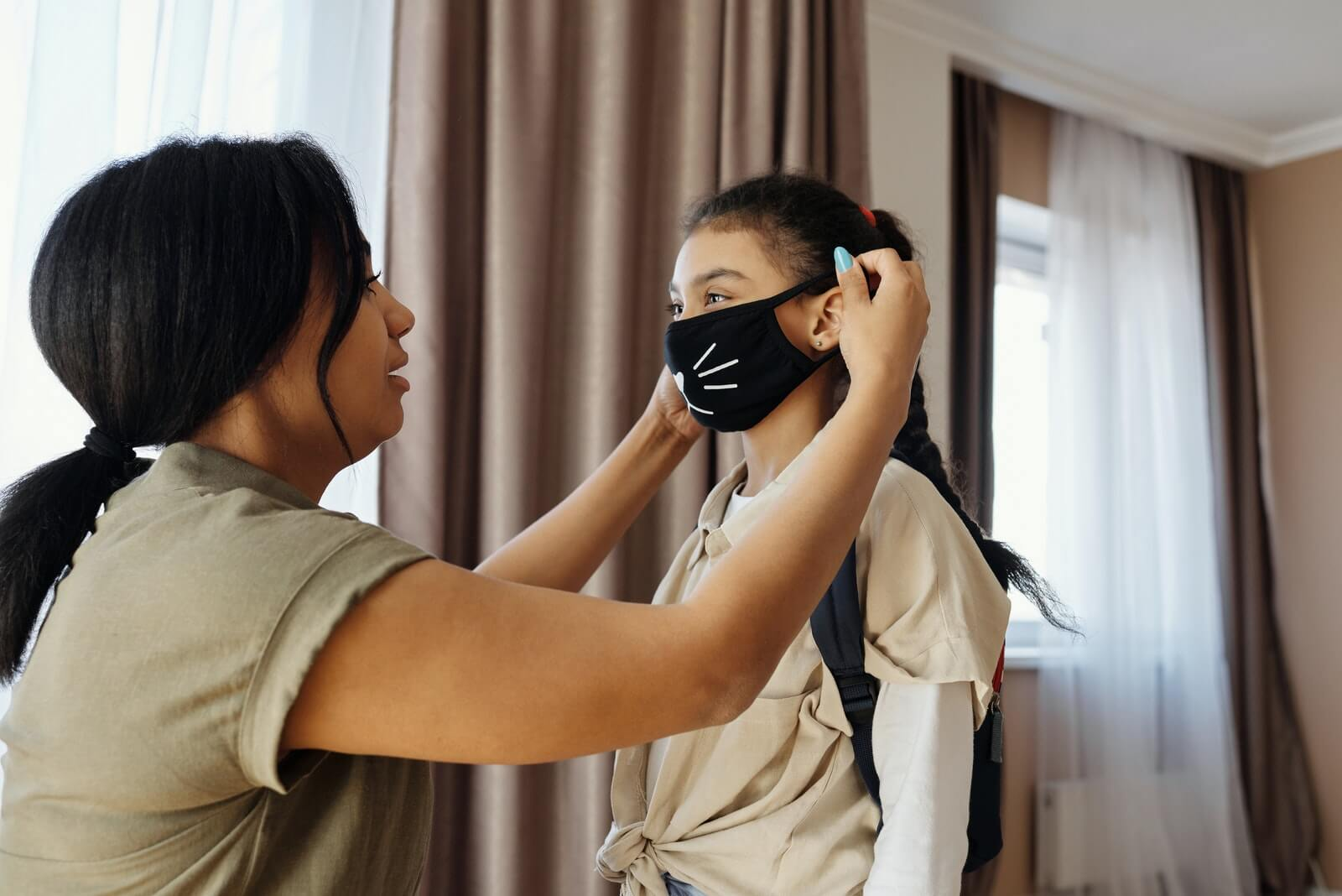 A woman helps her daughter put on a face mask during the COVID-19 pandemic