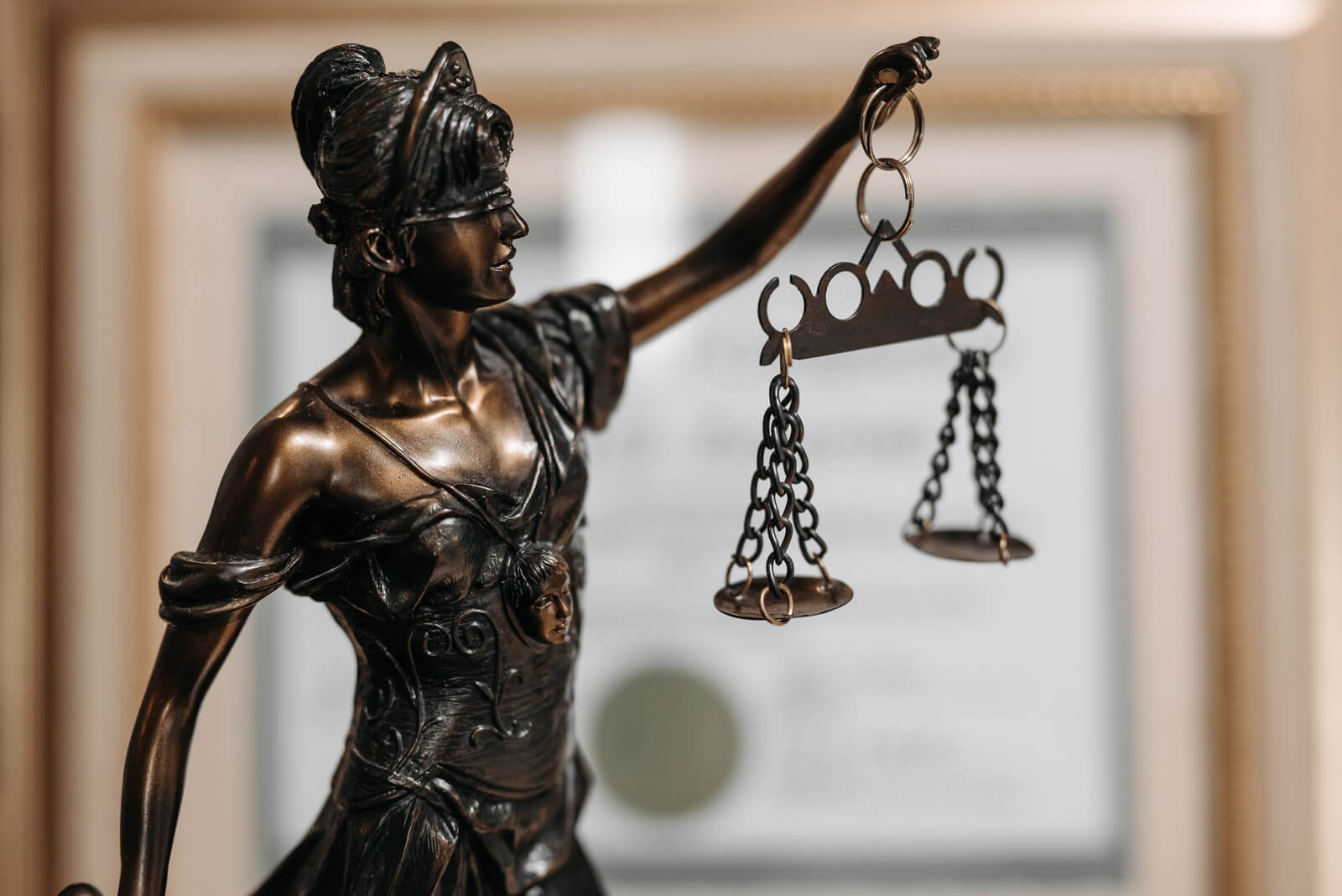 statuette of Justice holding balanced scales